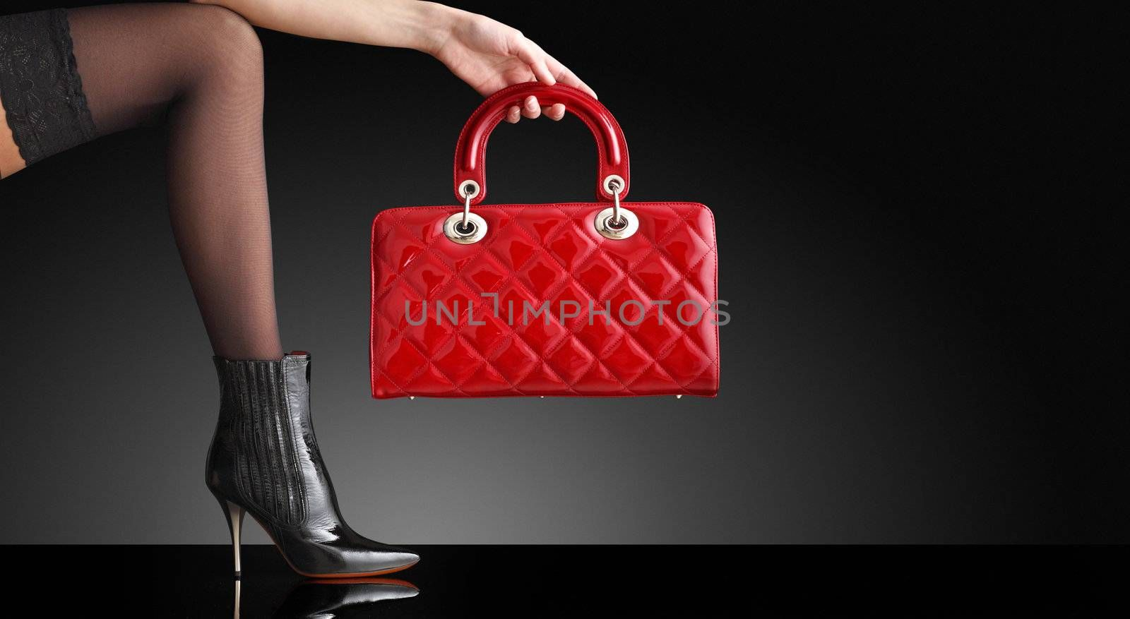 fashionable woman with a red handbag, only legs