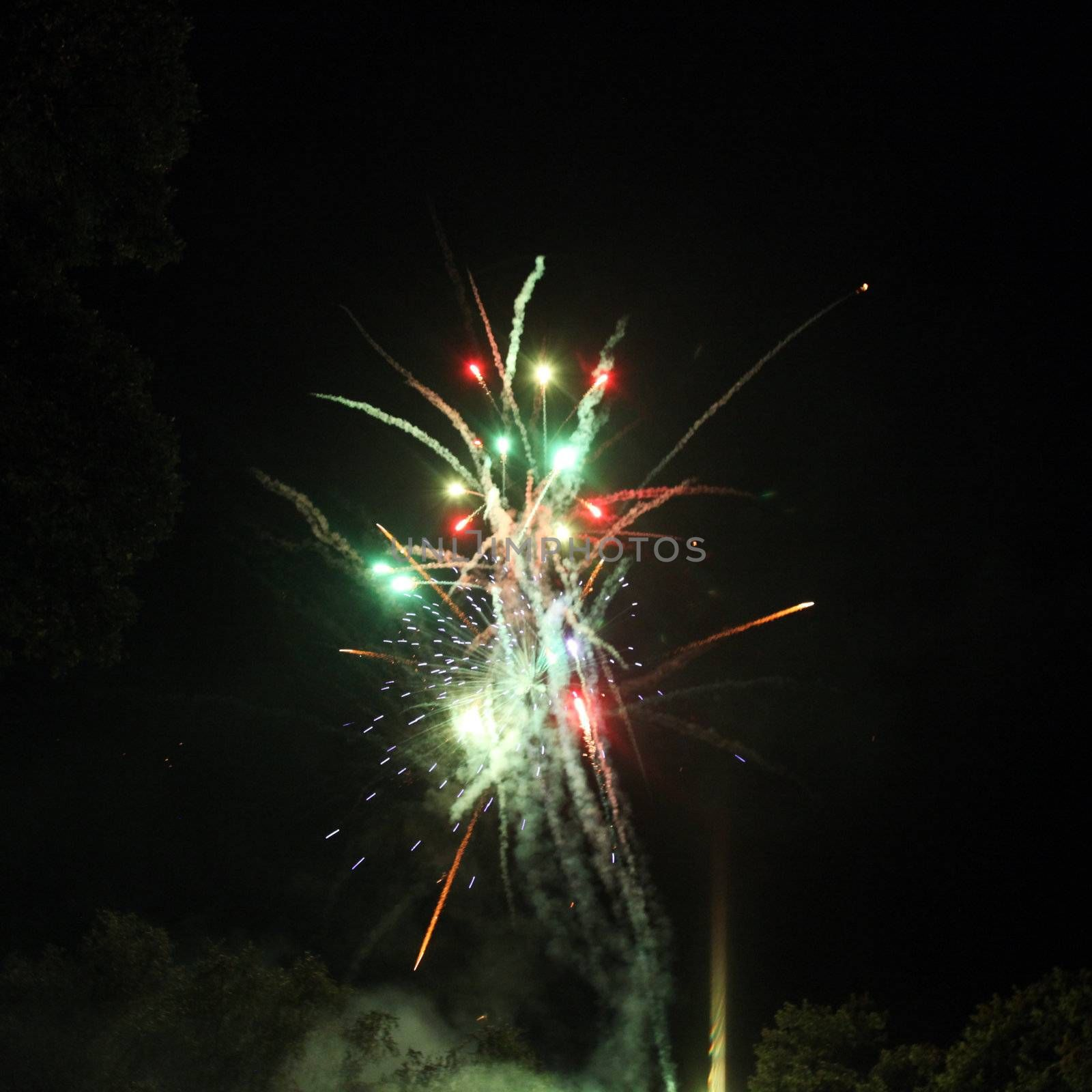 Colorful festive fireworks display lighting up the dark night sky with bursts of fiery red and green