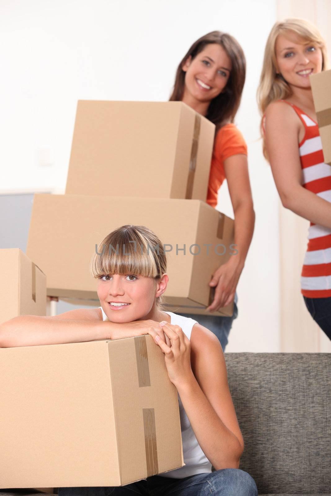 Three female flat-mates packing boxes