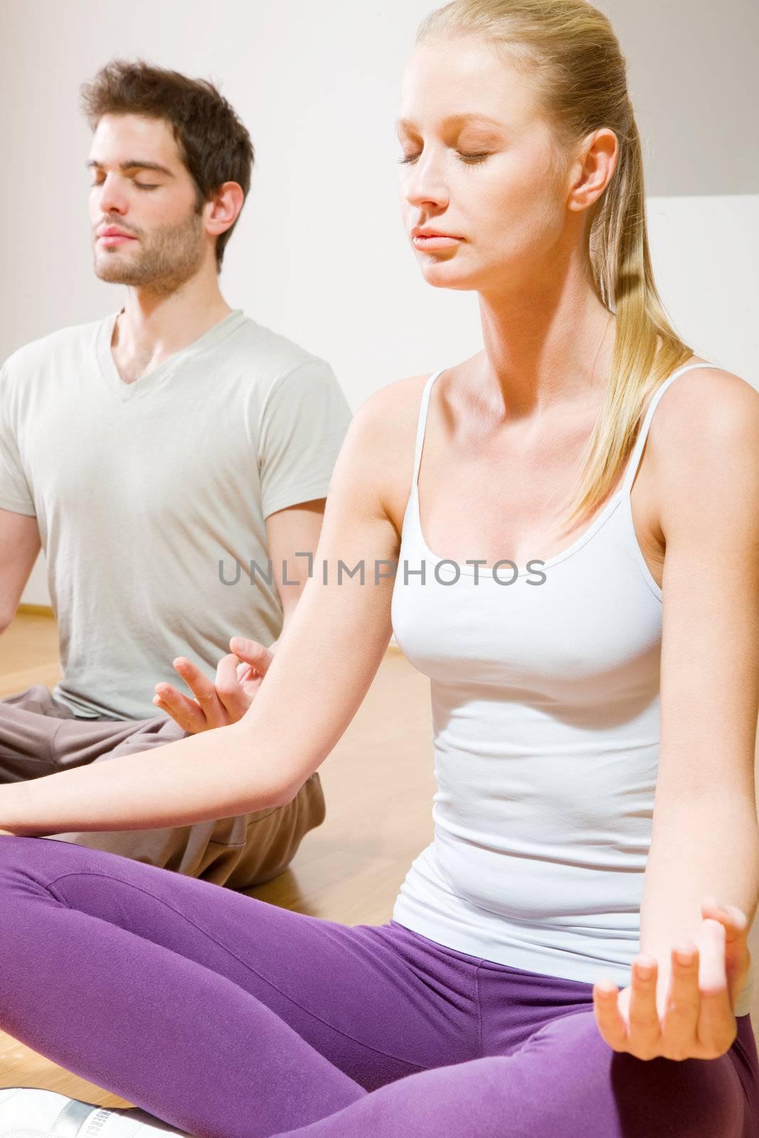 couple sitting on floor doing yoga