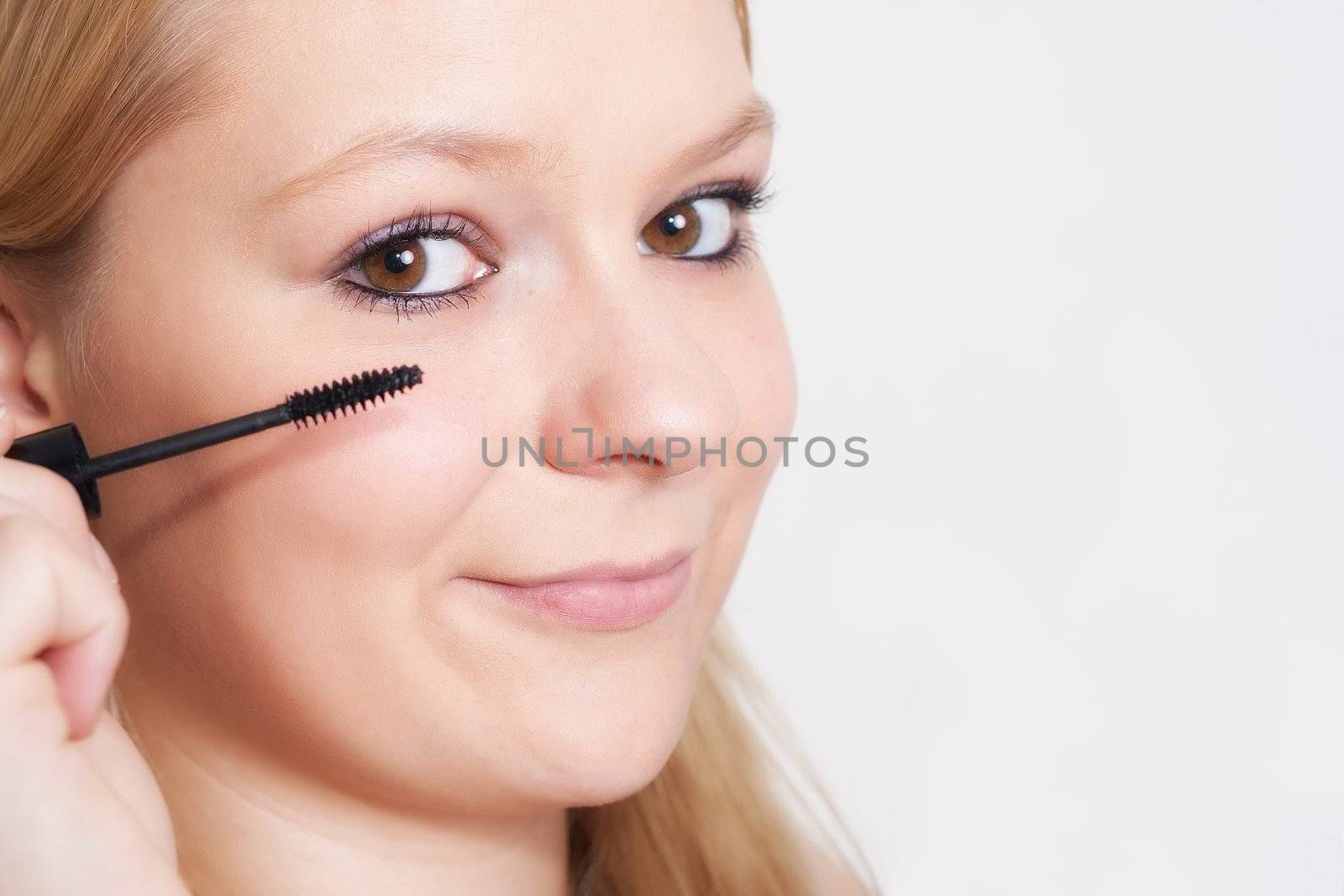 smile blonde young woman  with cosmetics looking