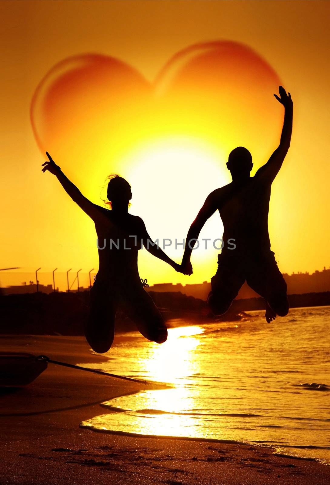 Happy young couple jumping, holding hands with heart shape in the sky, symbol of happiness, family playing outdoor, sunset on the beach, fun romantic honeymoon vacation, love concept