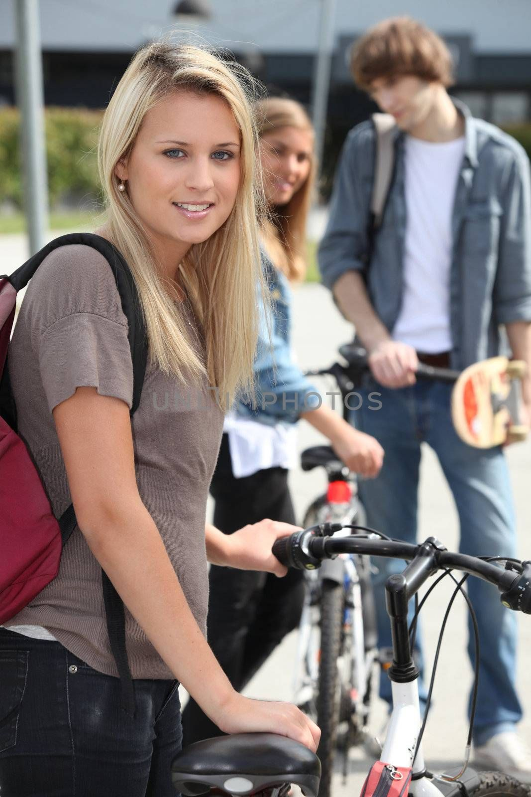 Blond female teenager stood by bicycle friends in background