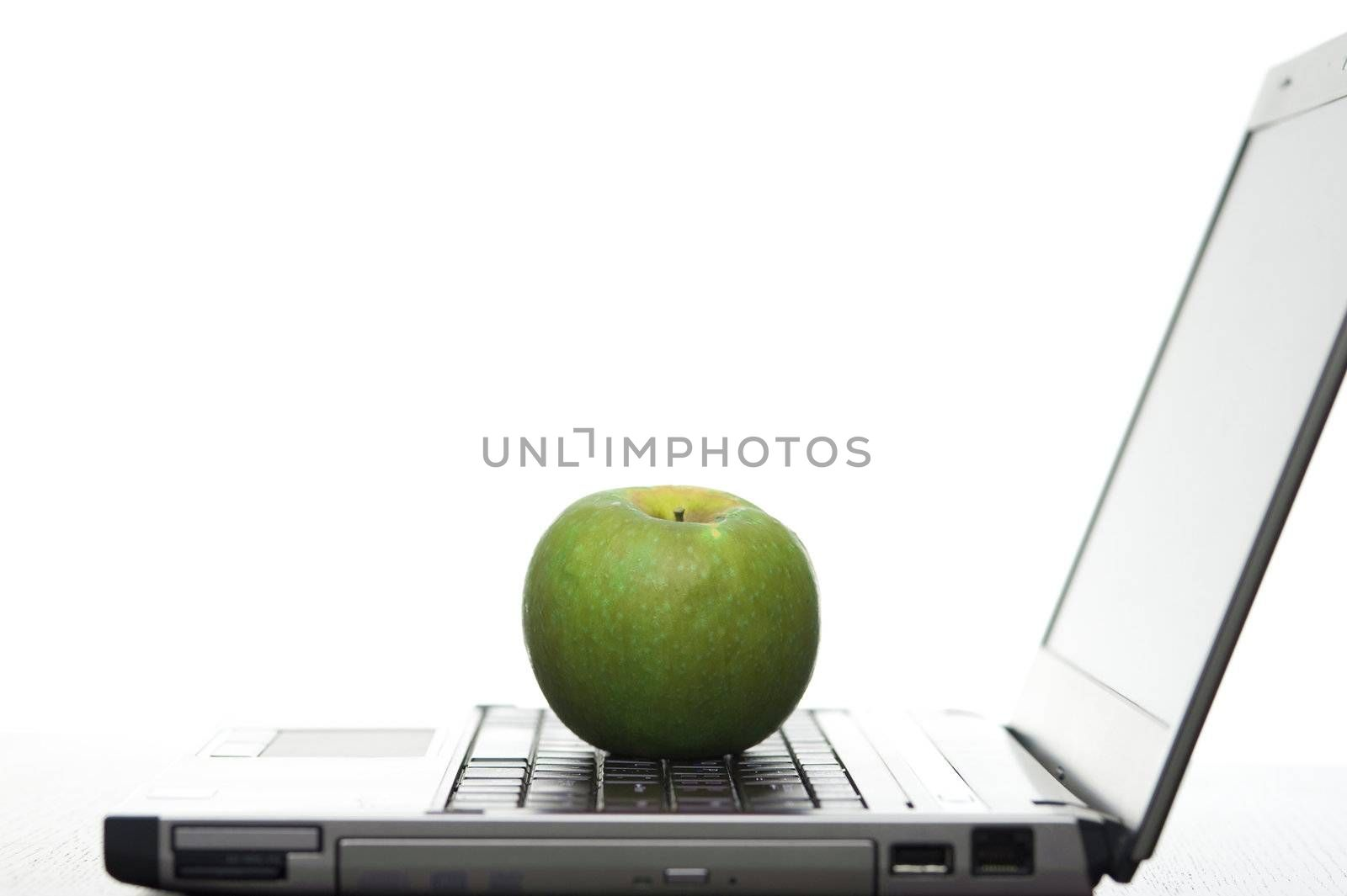 Open laptop sideways on with a fresh red apple creating a elearning concept.