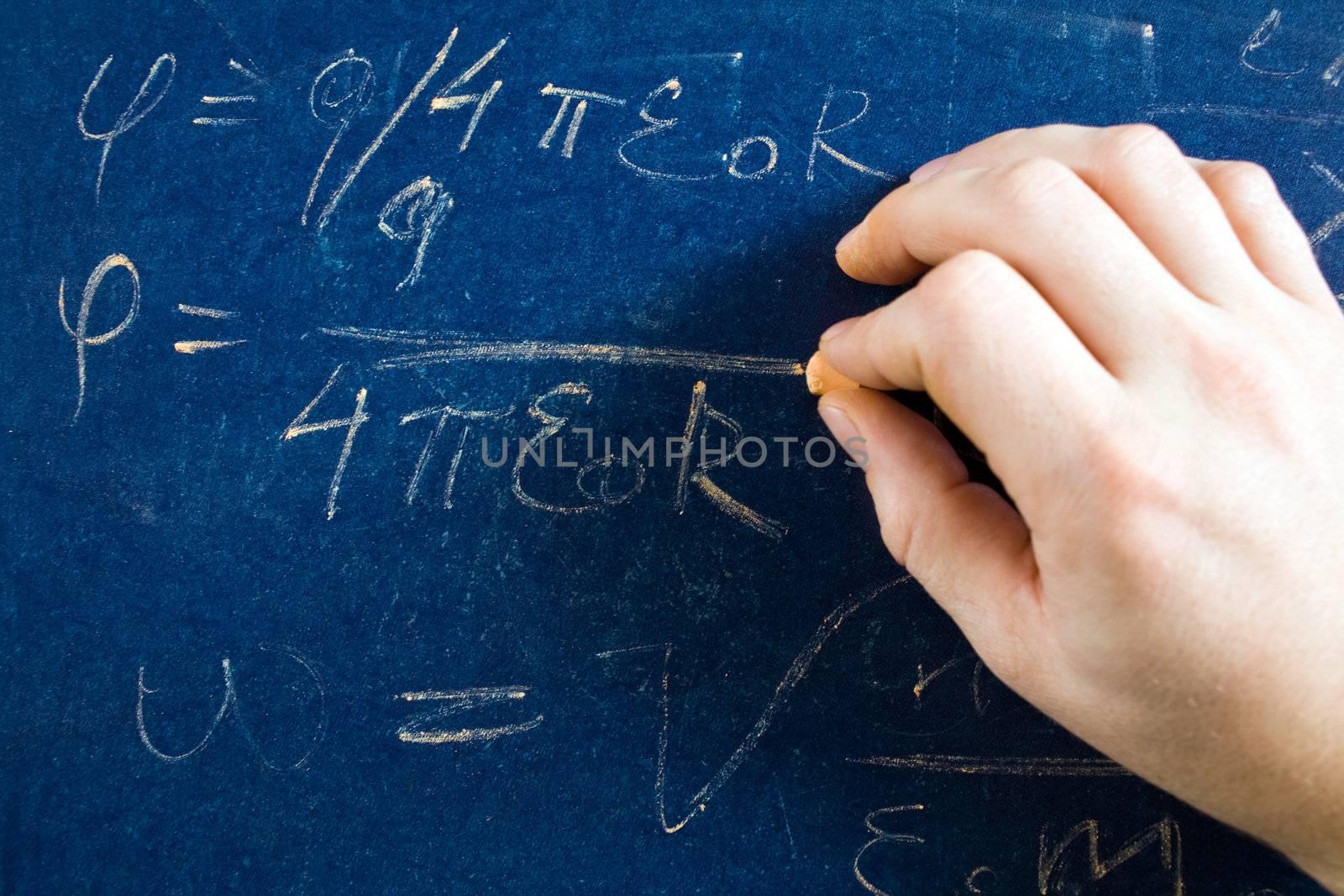 Stock photo: an image of a hand writing formula on a blackboard