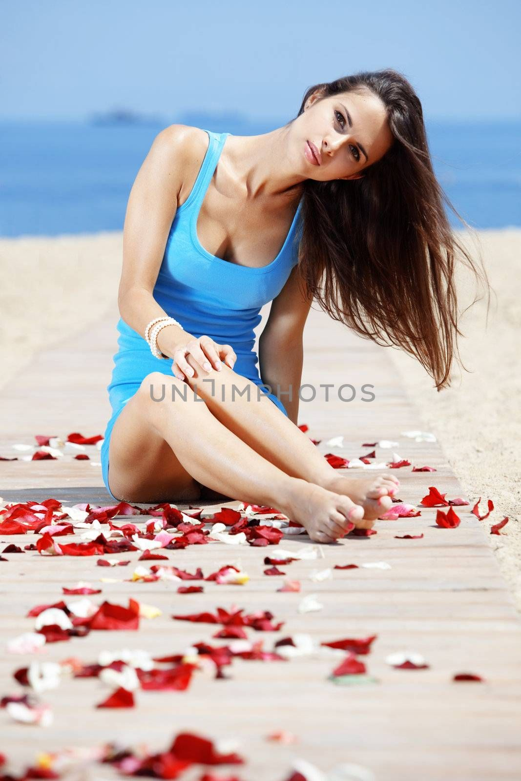 Portrait of young beautiful woman resting at the beach among rose petals
