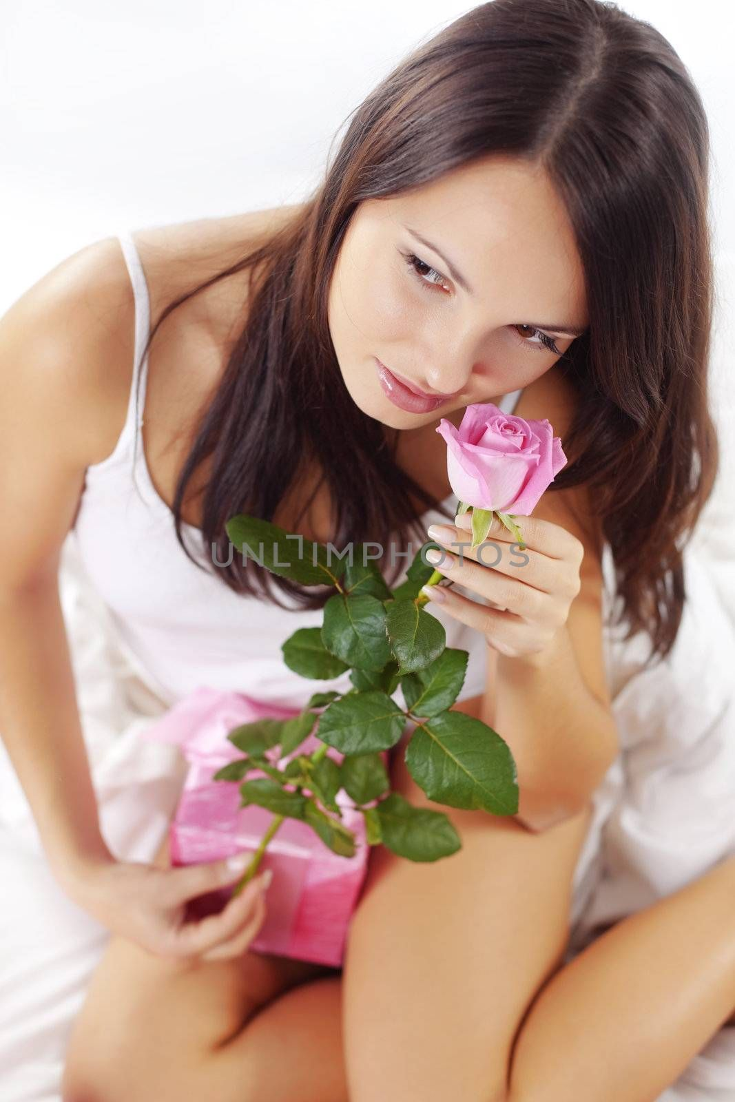 Portrait of beautiful woman smelling rose on bed in morning