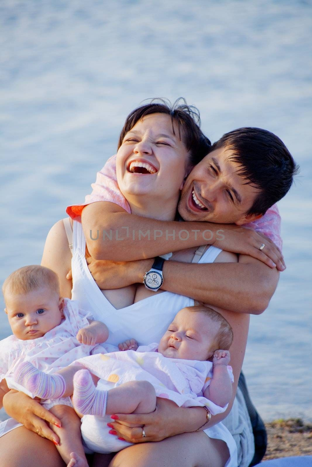 Happy family playing with two infant babies