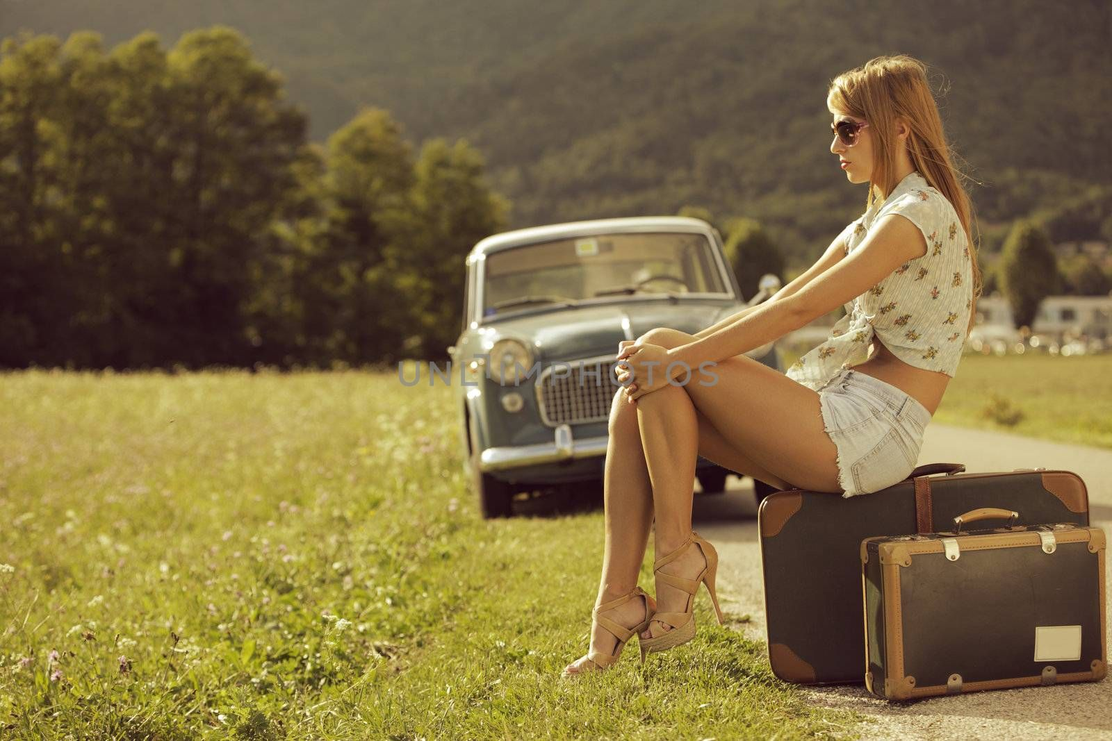 Young sexy woman sitting on suitcases at the roadside, vintage cars in the background