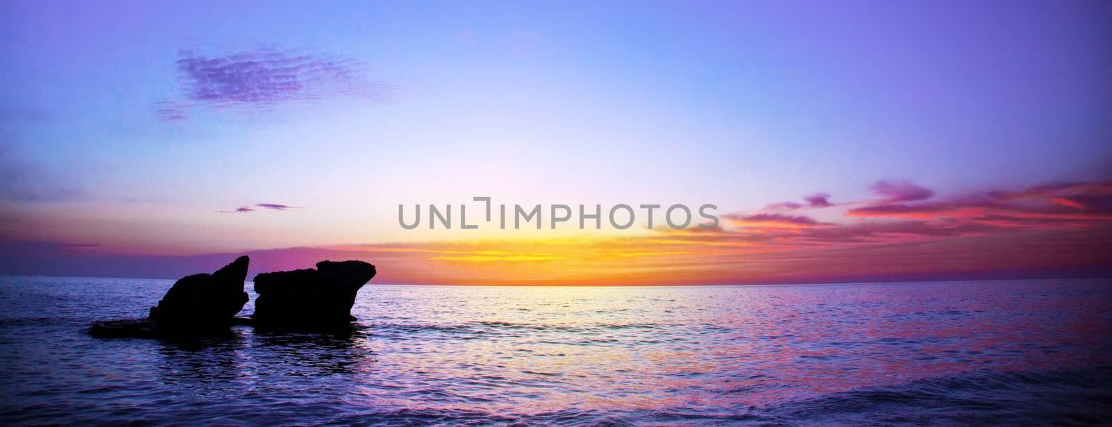 Picture of romantic purple sunset over seascape, peaceful ocean landscape, beautiful rocks in evening sea, calm autumn weather, violet dusk on coastline, night scenery of mediterranean sea, travel concept