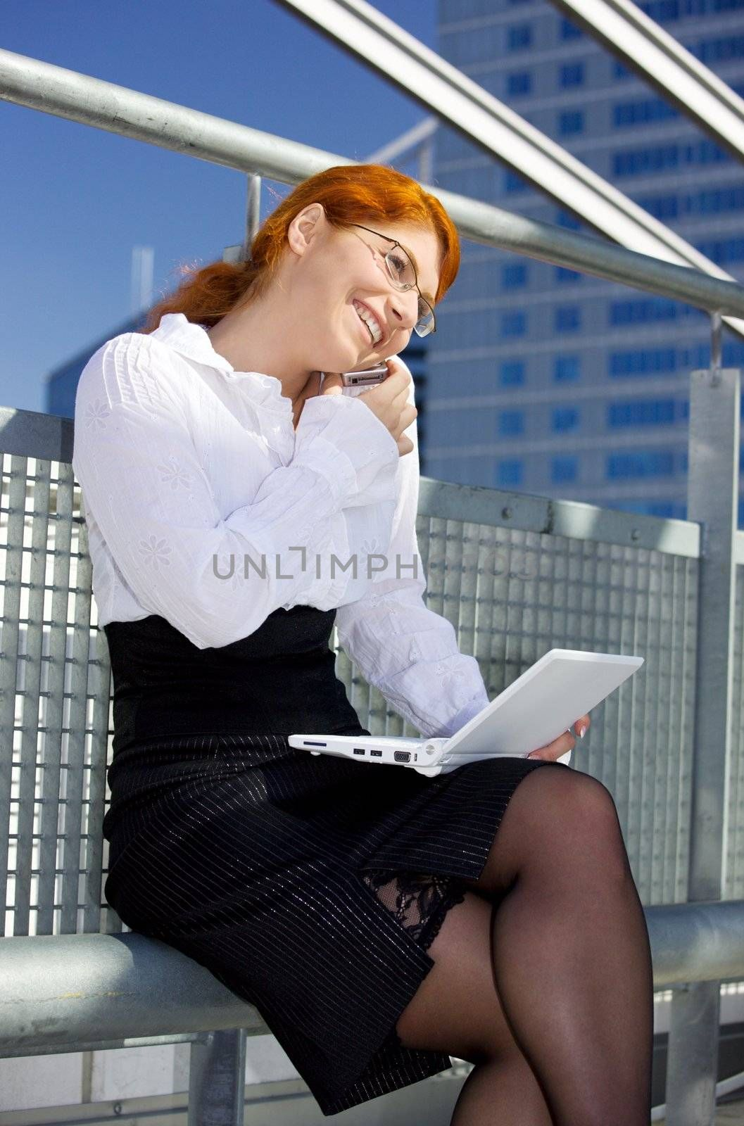 picture of lovely businesswoman with cell phone and laptop