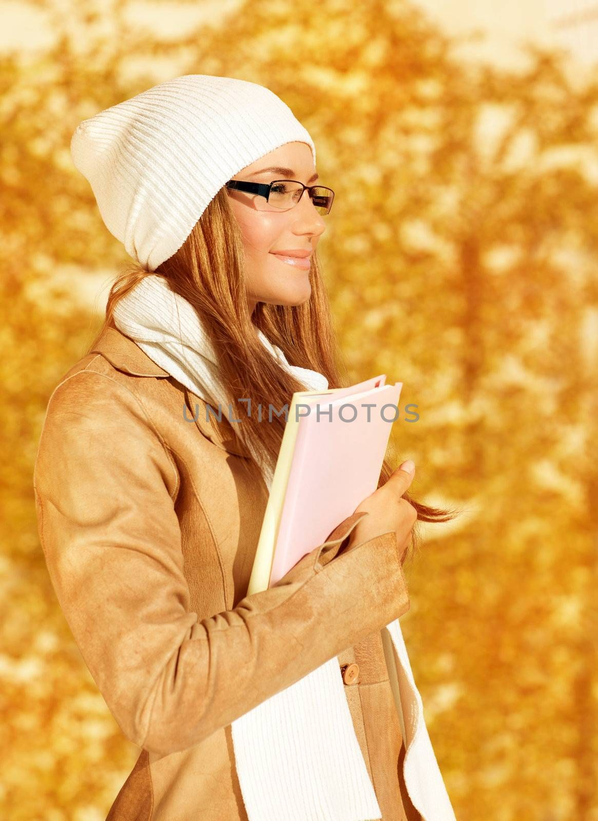 Photo of pretty student girl standing in autumn park and holding books in hands, young businesswoman on golden foliage background, smiling teenager enjoying education time, fall season