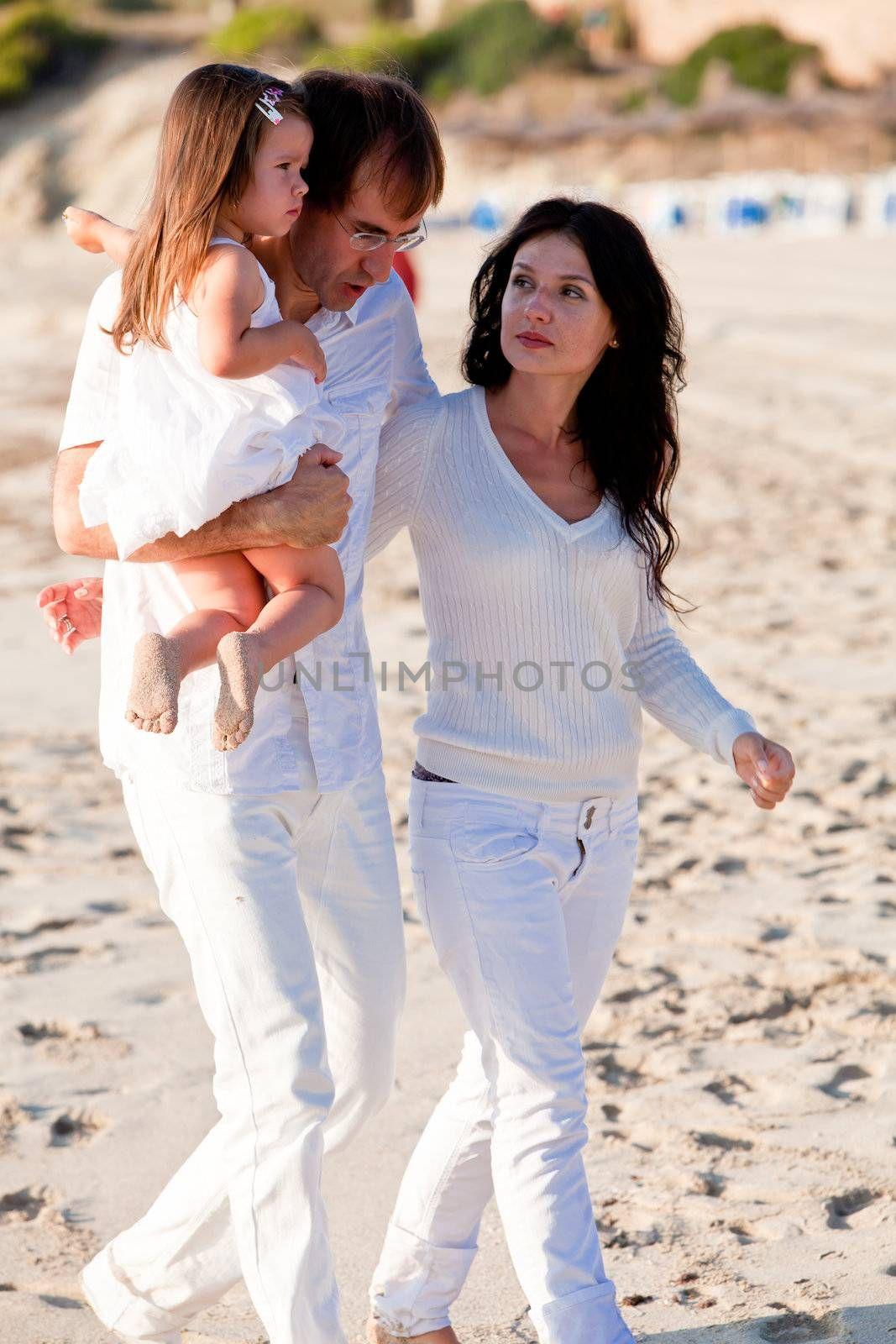 happy young family with daughter on beach in summer lifestyle