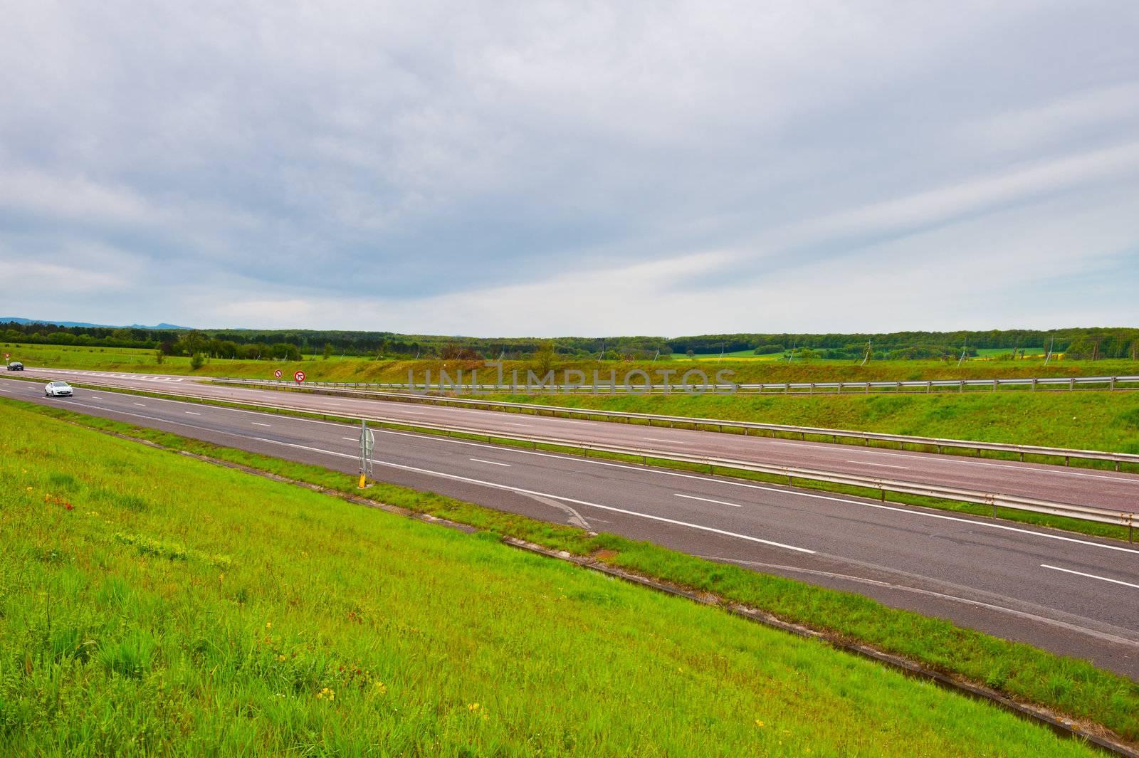 Straight Asphalt Road between Fields in Belgium