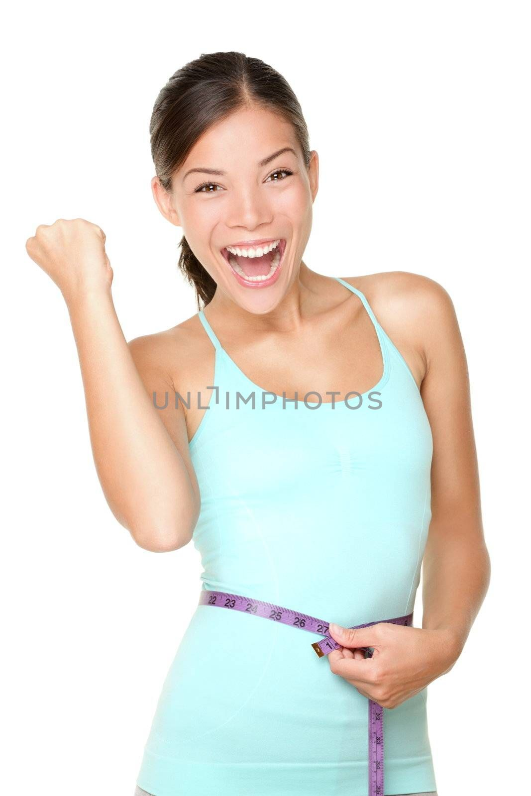 Weight loss concept woman smiling happy excited holding measuring tape around waist. Energetic portrait of sport fitness model isolated on white background. Mixed race Caucasian / Asian woman.