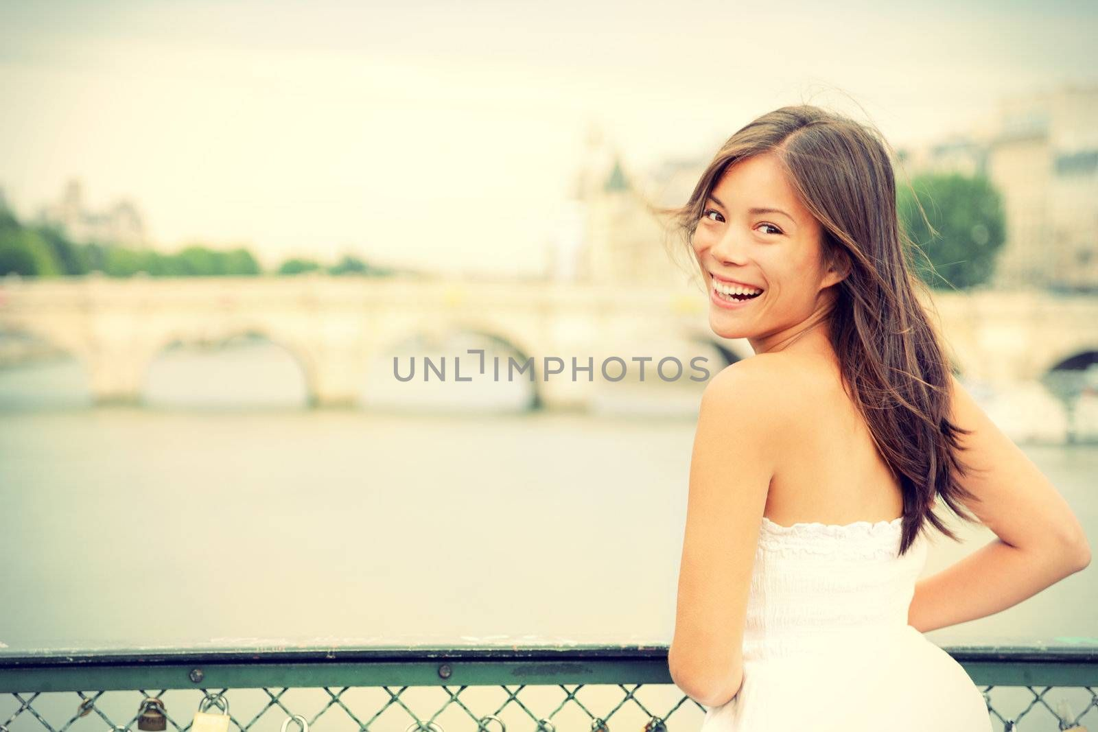 Paris woman laughing joyful and candid in Paris on brige on river Seine. Fresh energetic young mixed race Asian Caucasian female model joyful.