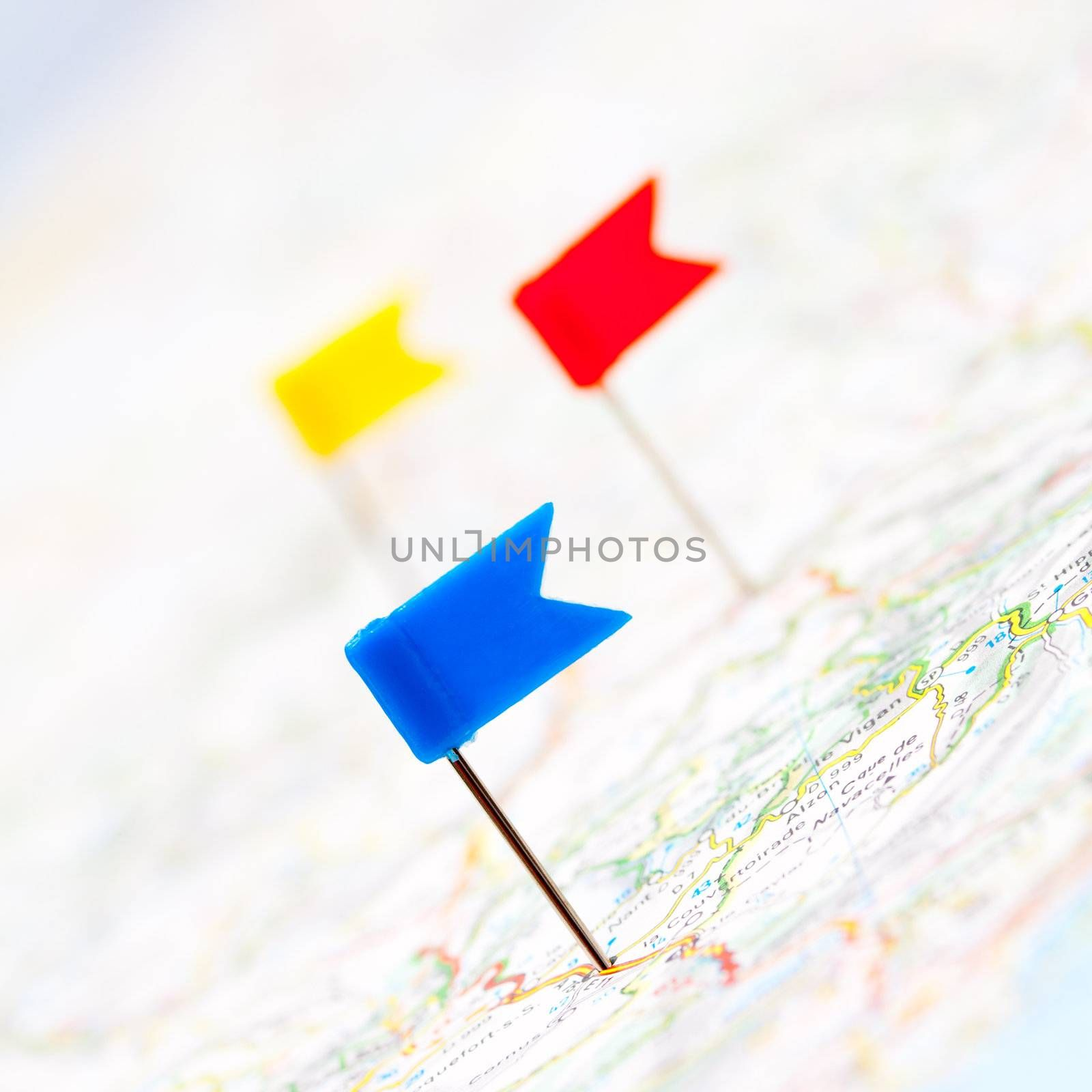 Three color flag pins on a map, shallow focus
