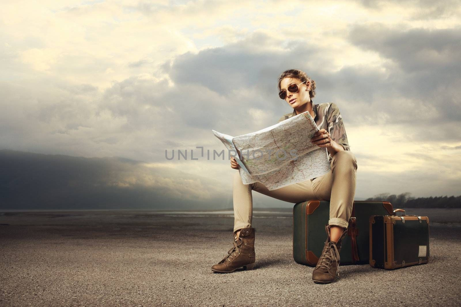 Beautiful young woman sitting on a suitcase