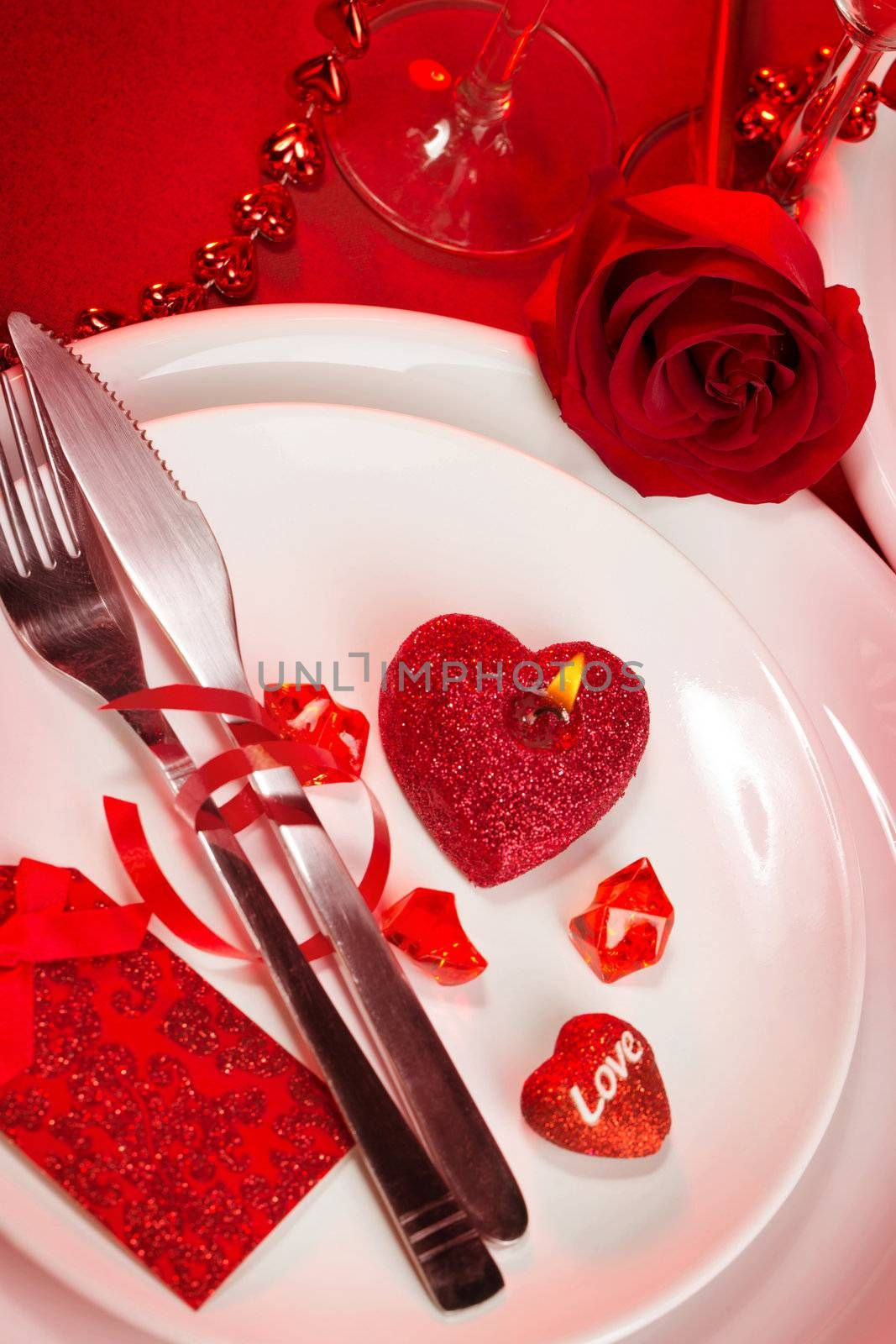 Photo of beautiful romantic table setting, luxury white utensil served with silver knife and fork and decorated with heart-shaped candle and red rose, Valentine day, romantic holiday, love concept