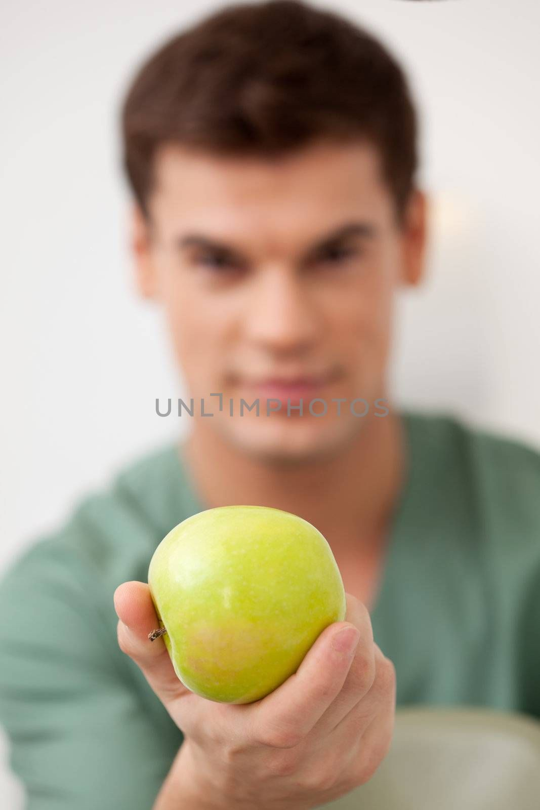 Dentist holding an apple out to the viewer, shallow depth of field, focus on apple