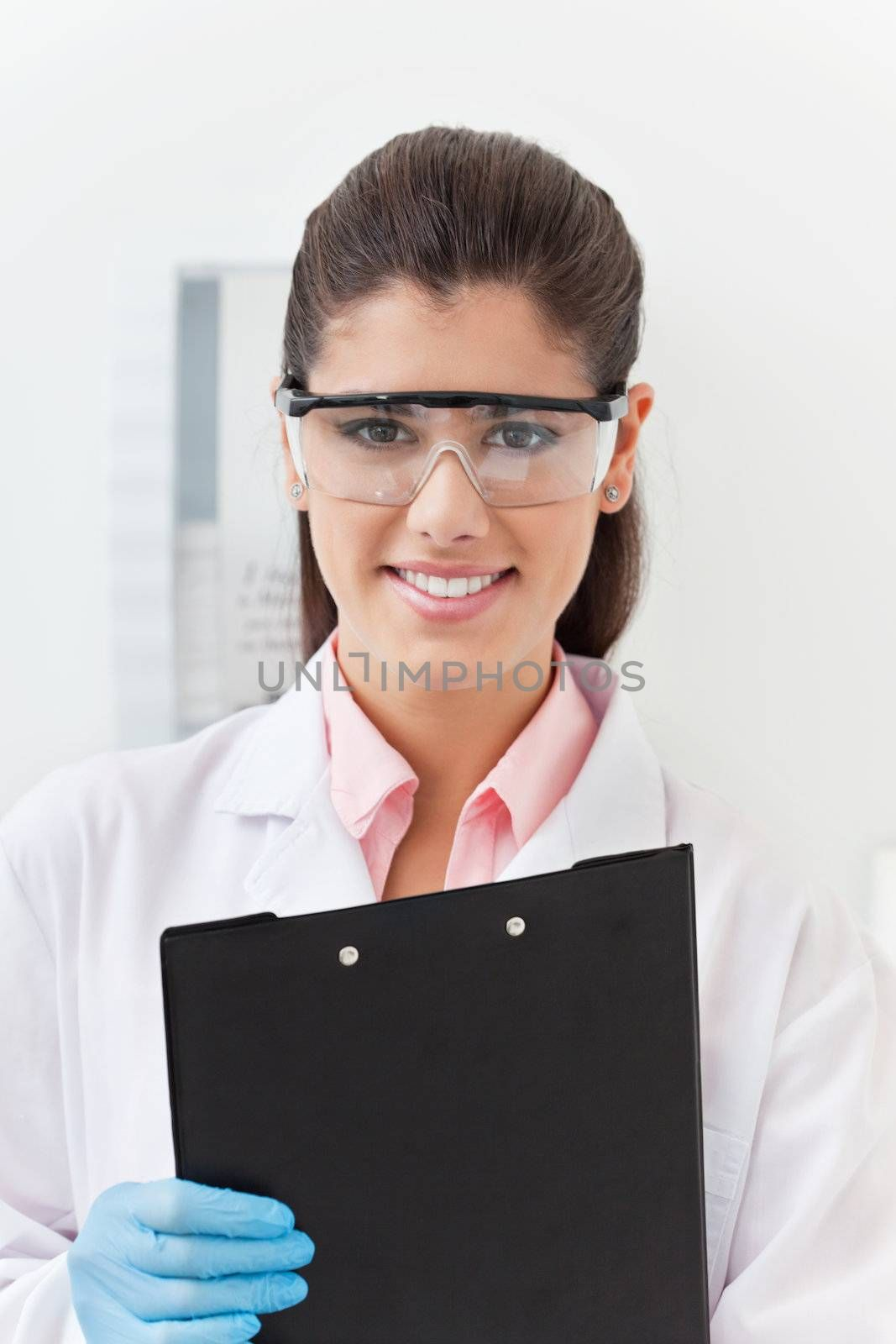 Smiling confident young dentist holding clipboard