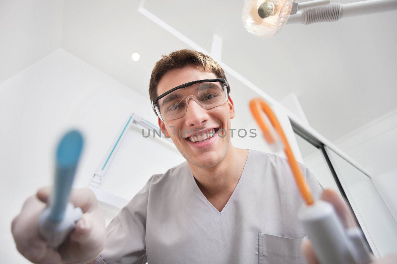 Close-up of young smiling dentist holding dental tools