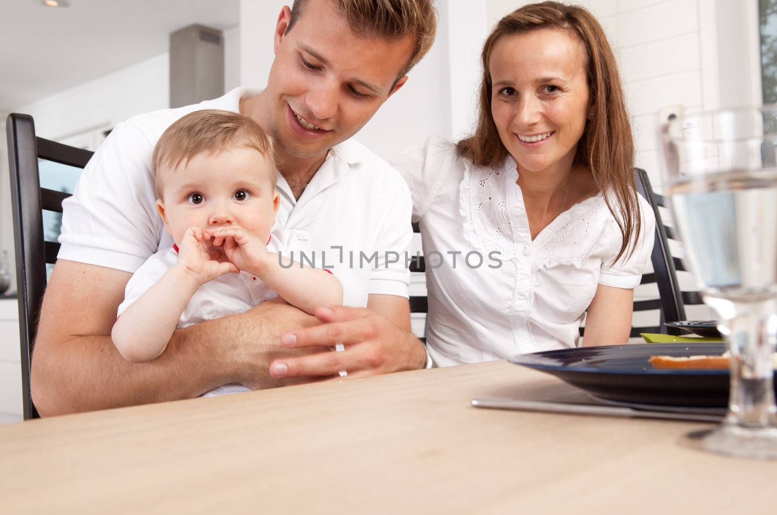 Portrait of happy small family at home at dinner table