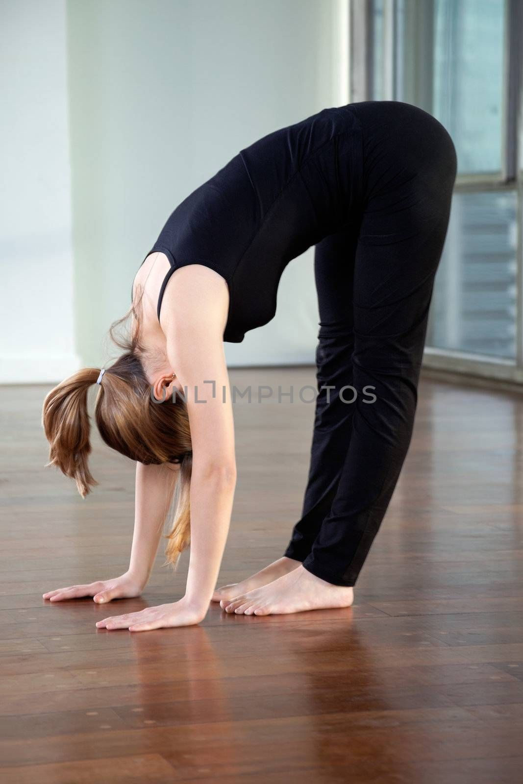 Full length of a young woman doing Standing Forward Bend in gym