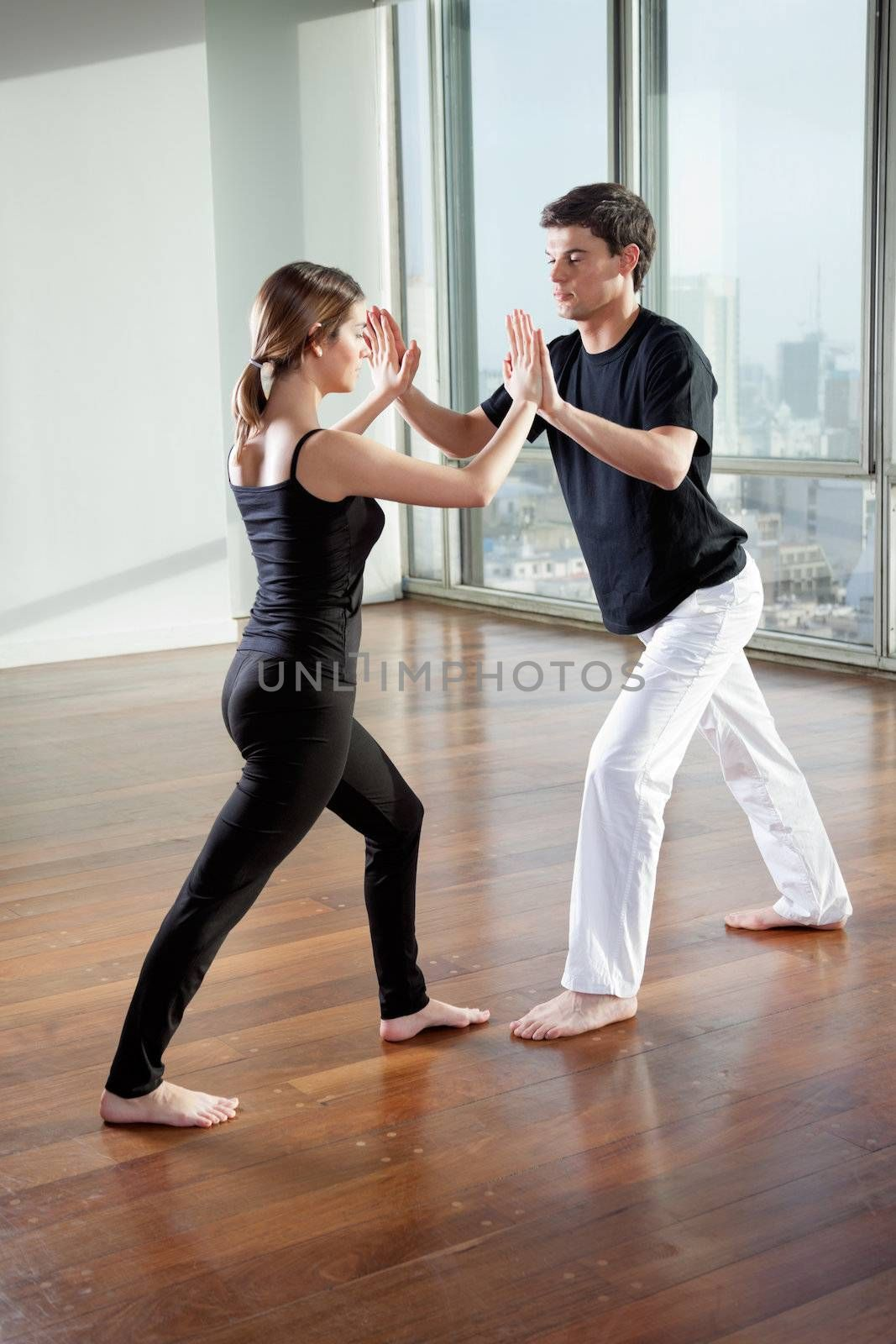 Full length of young yoga partners practicing yoga exercise at gym