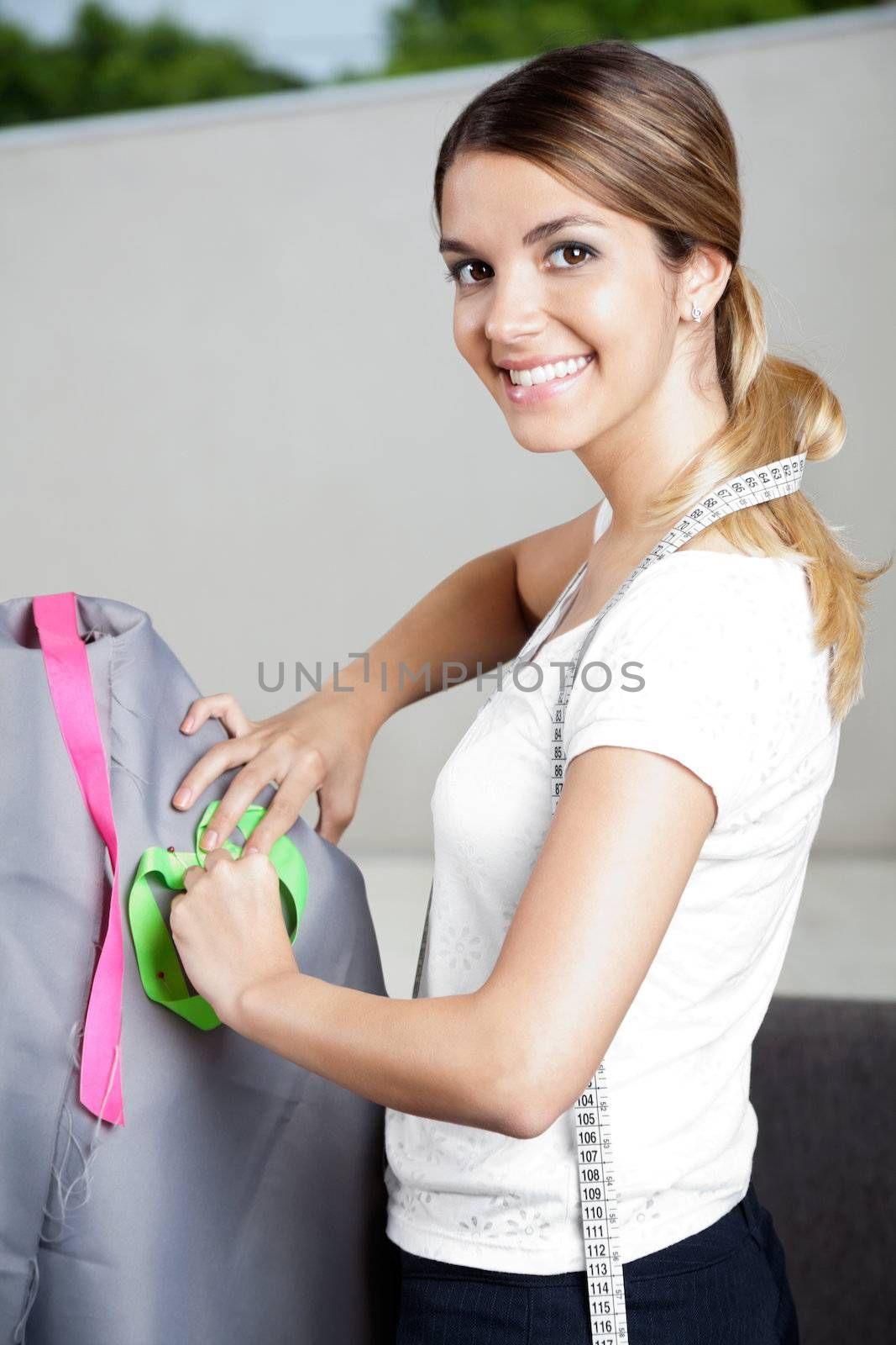Portrait of pretty female fashion designer working on a mannequin with gray fabric