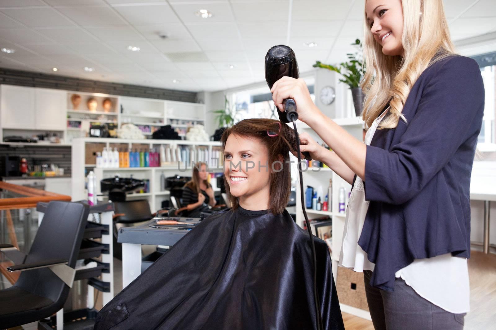Hairdresser drying female customer's hair in beauty salon