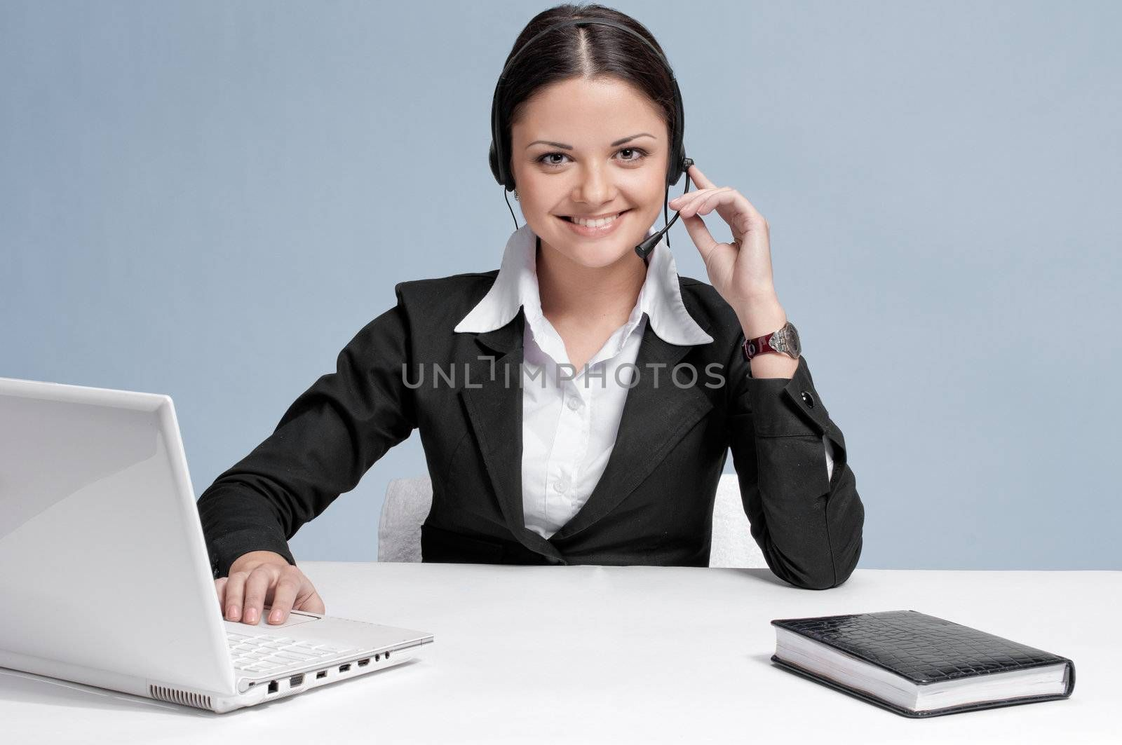 Busy business woman in office place talking by wireless headset over white table, laptop and diary. Smile