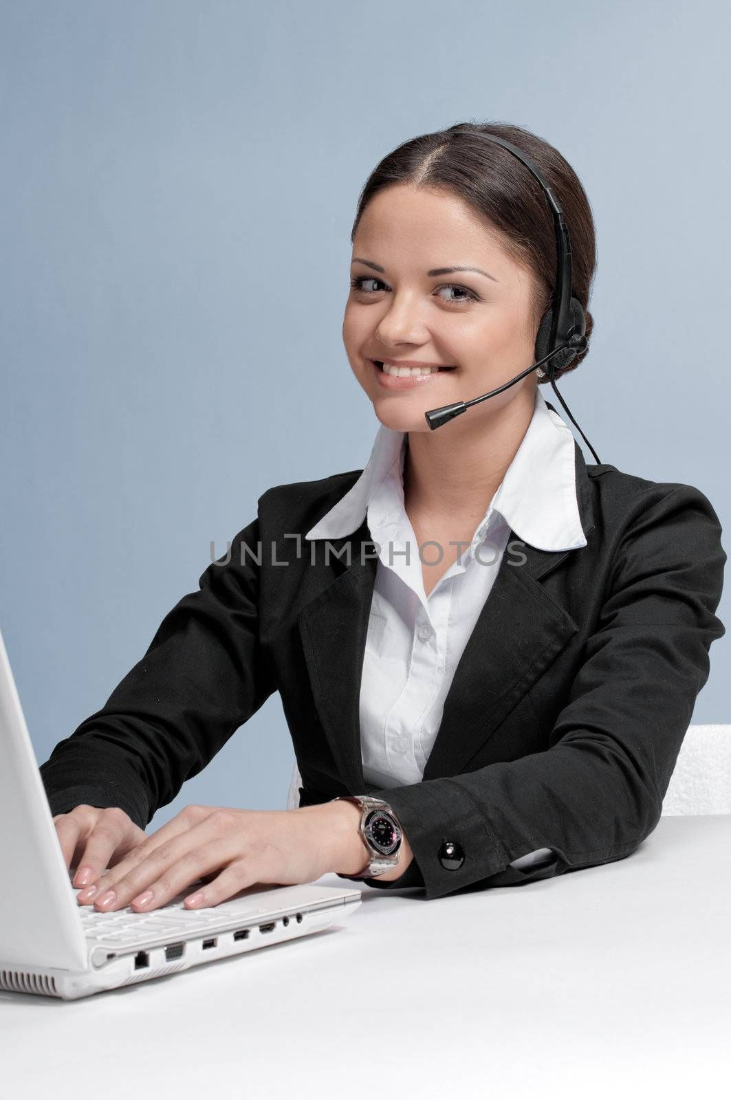 Busy business woman in office place communicate by wireless headset over white table, laptop and diary