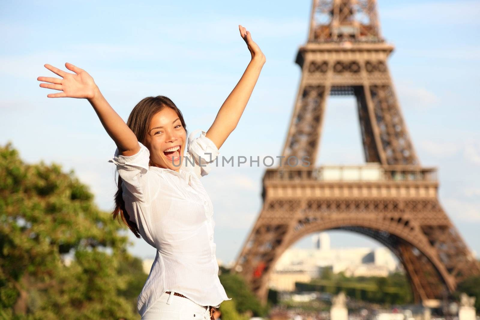 Travel Paris Eiffel Tower woman. Happy tourist on travel holidays cheering joyful with arms raised up excited. Beautiful multiracial Asian Caucasian woman traveler in tourism concept.