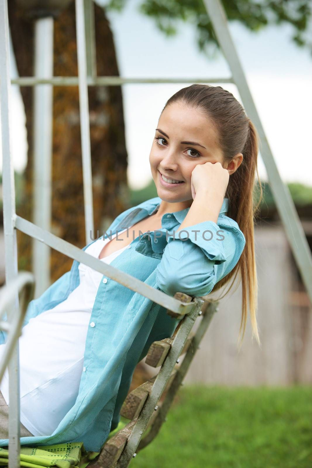 Portrait of young woman sitting on seesaw