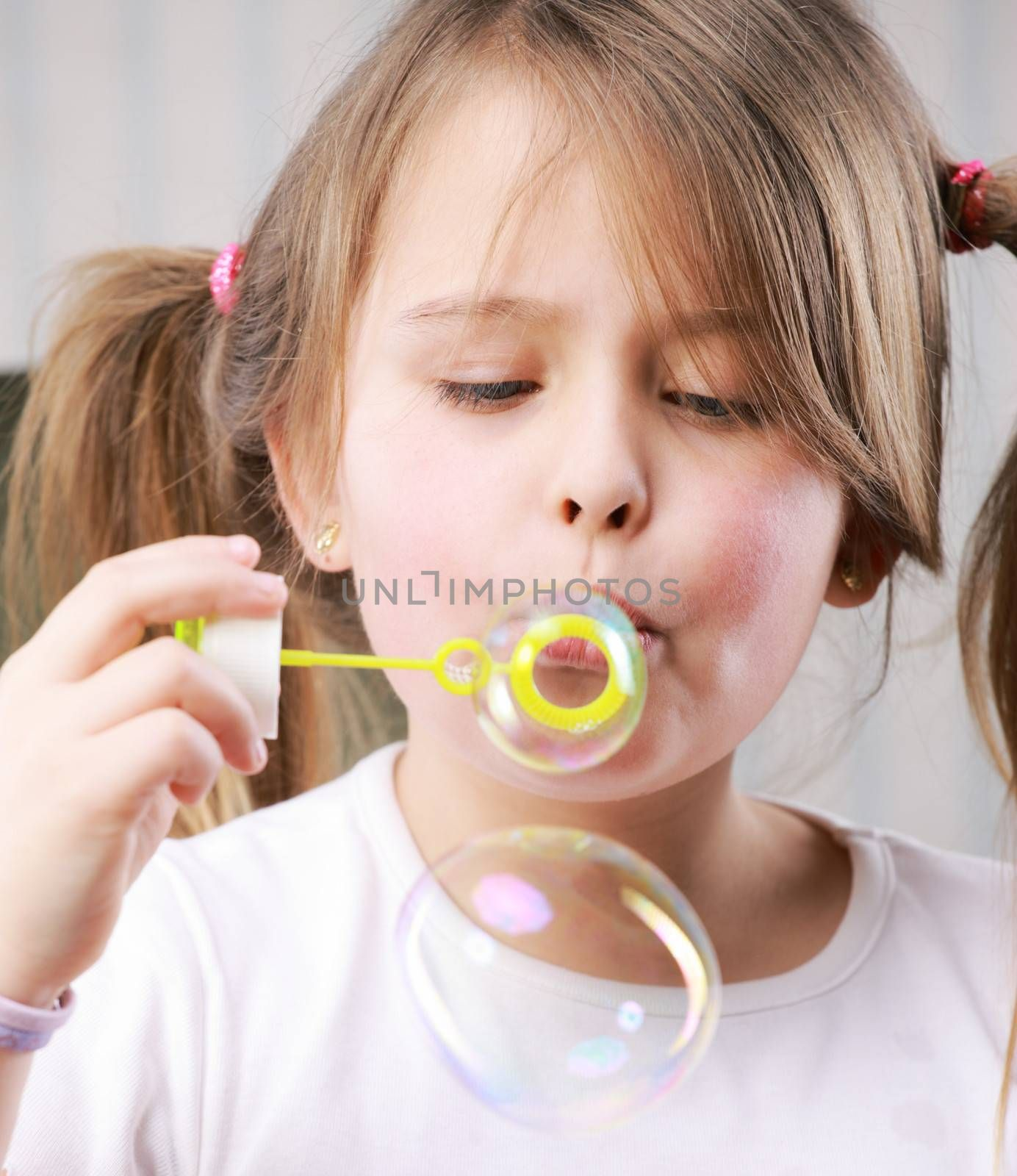 Portrait of a little girll blowing bubbles