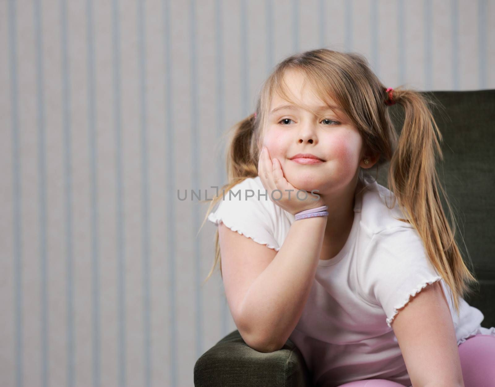 Portrait of a little beautiful girl sitting on armchair