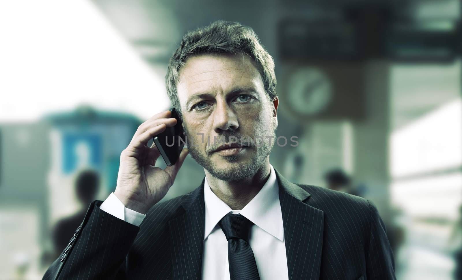 Portrait of a mature business man talking on phone at train station