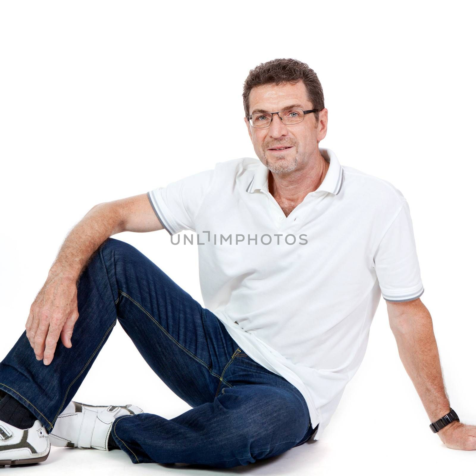 attractive healthy adult man sitting on floor with glasses and jeans t-shirt casual lifestyle isolated