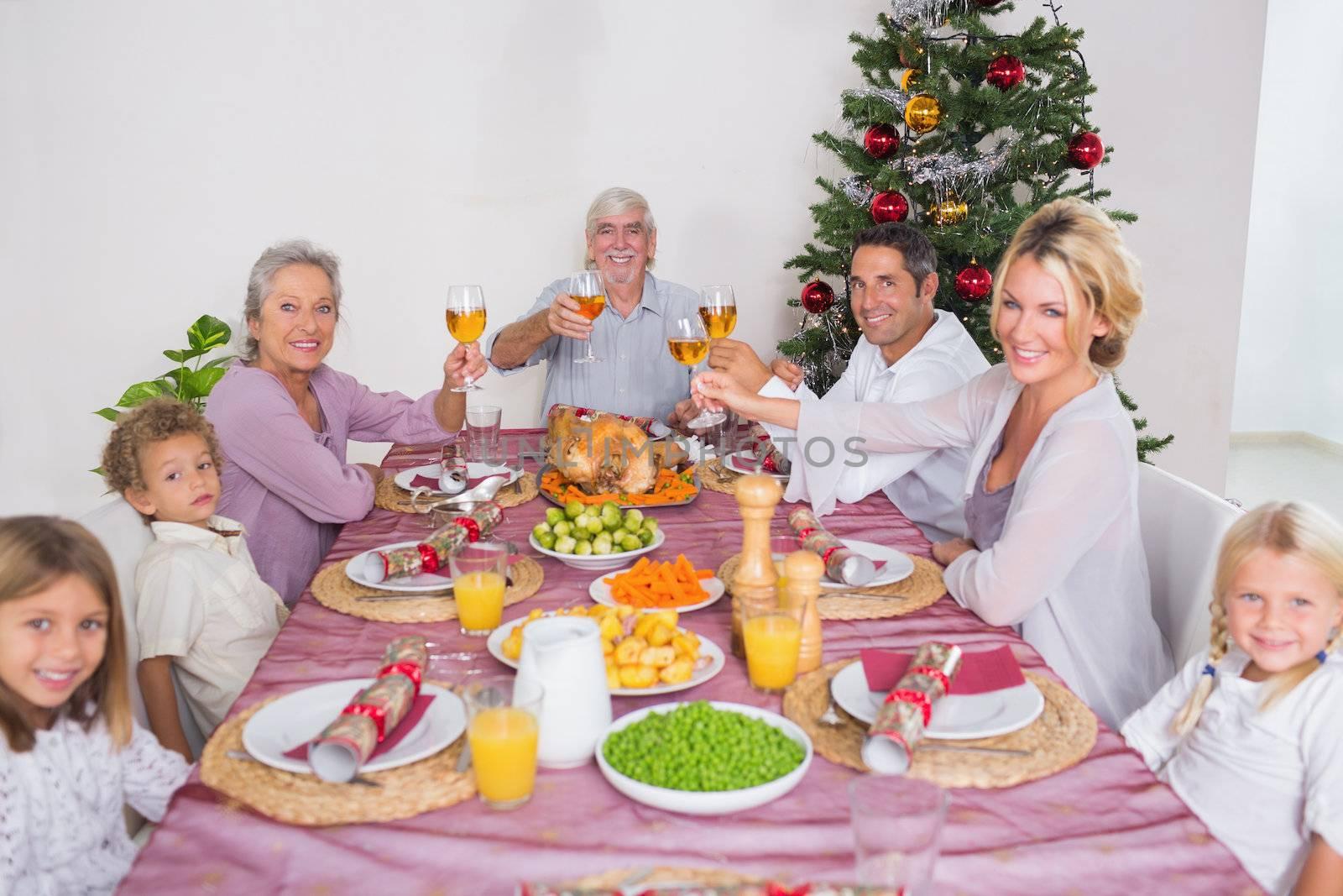 Family raising their glasses at christmas at dinner