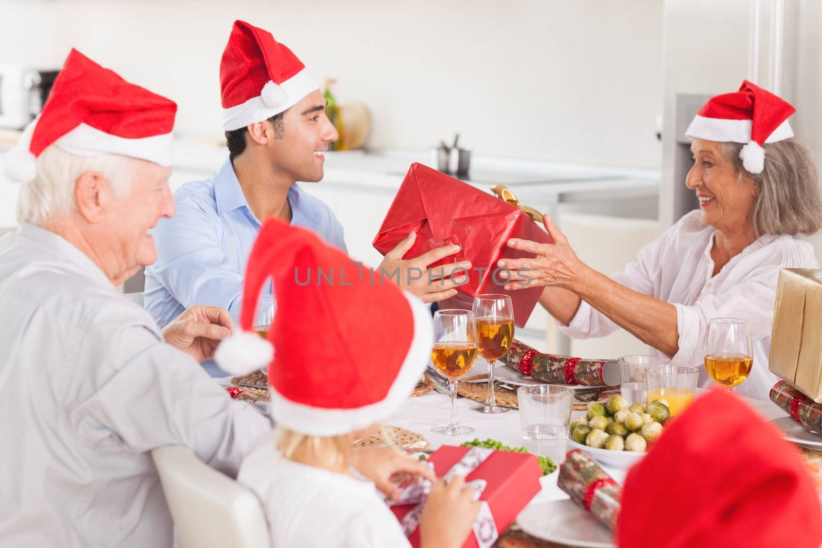 Happy family exchanging gifts at christmas time around the dinner table