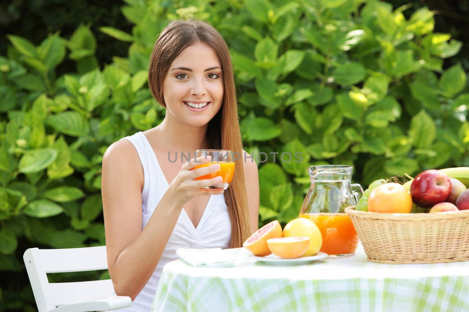 Young woman relaxes in the garden drinking a orange juice