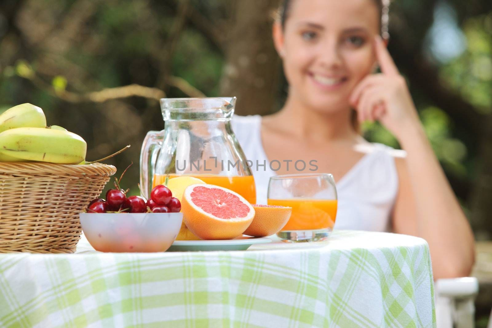 Table with fruit and orange juice, smiling woman on background