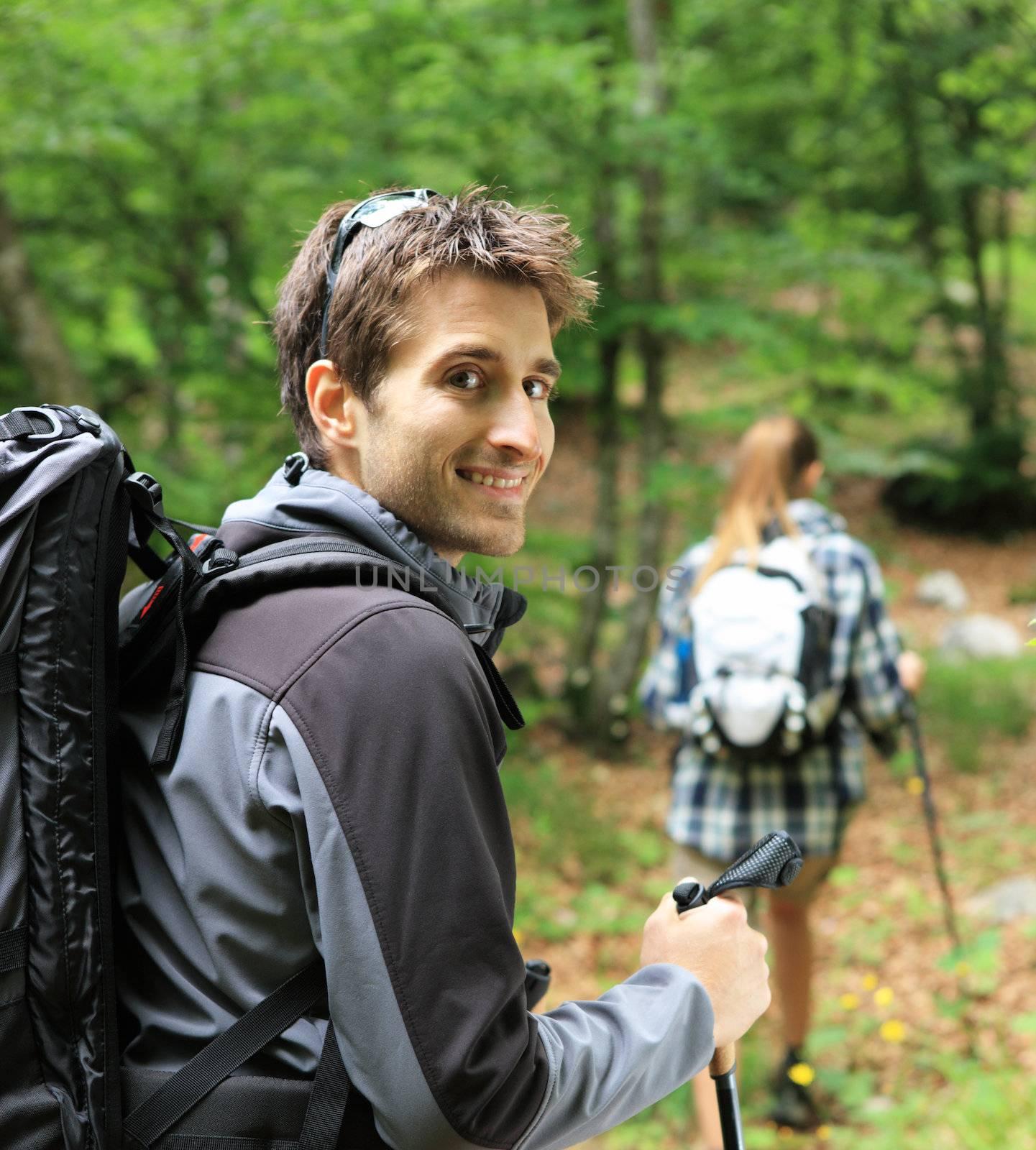 Young couple enjoying a nordic walk, man looking at camera and smiling