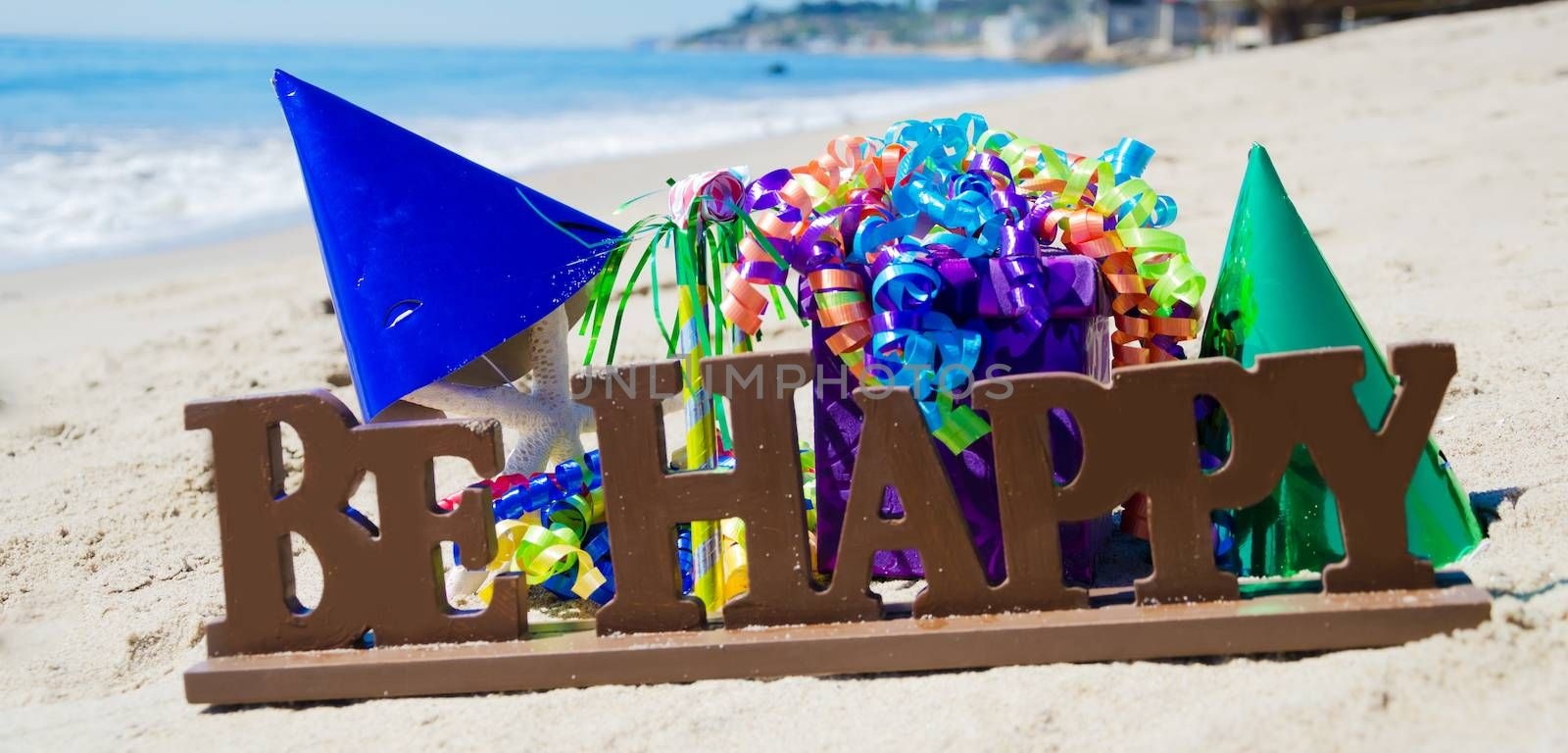 """Sign """"Be Happy"""" with Birthday decorations on the beach by the ocean"""