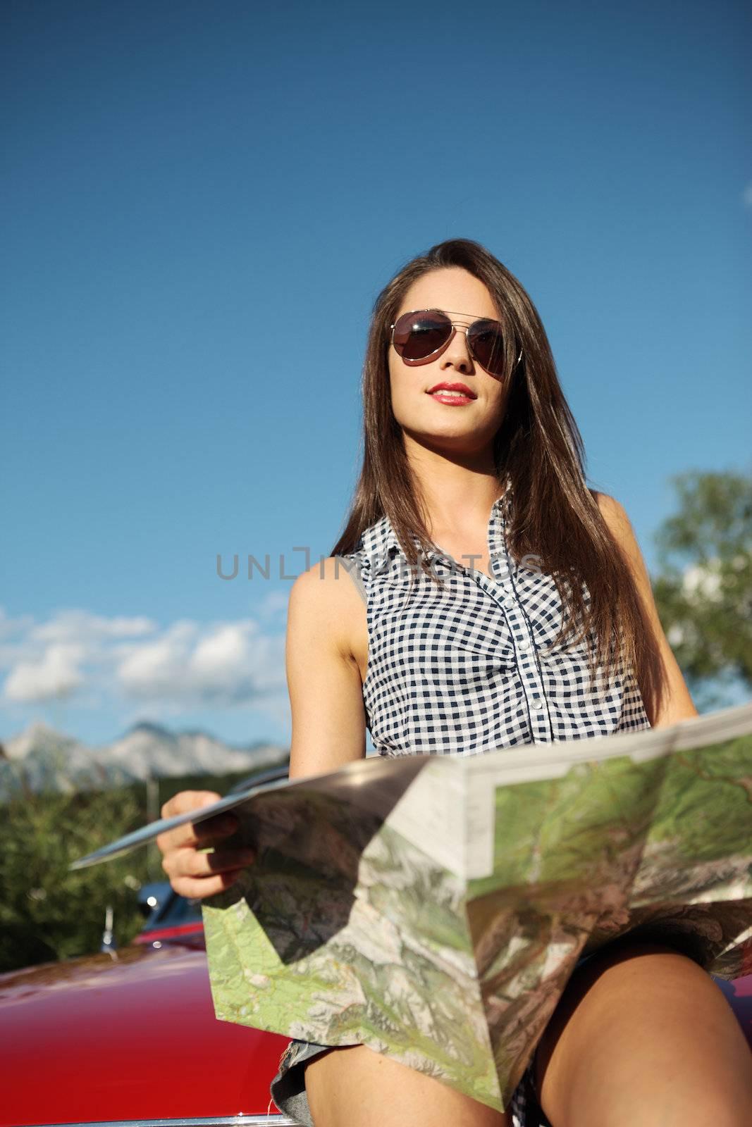 Young beautiful woman wearing sunglasses reading a roadmap