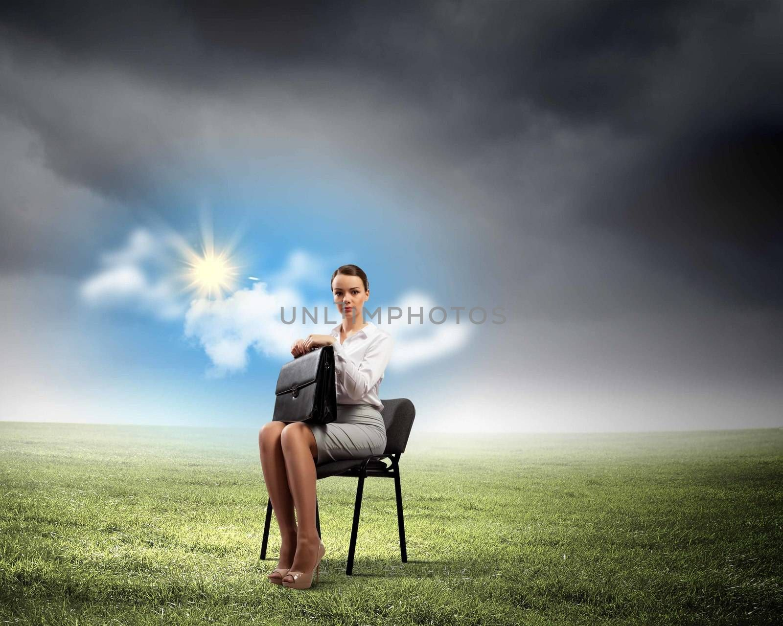 Image of young businesswoman sitting in chair holding suitcase