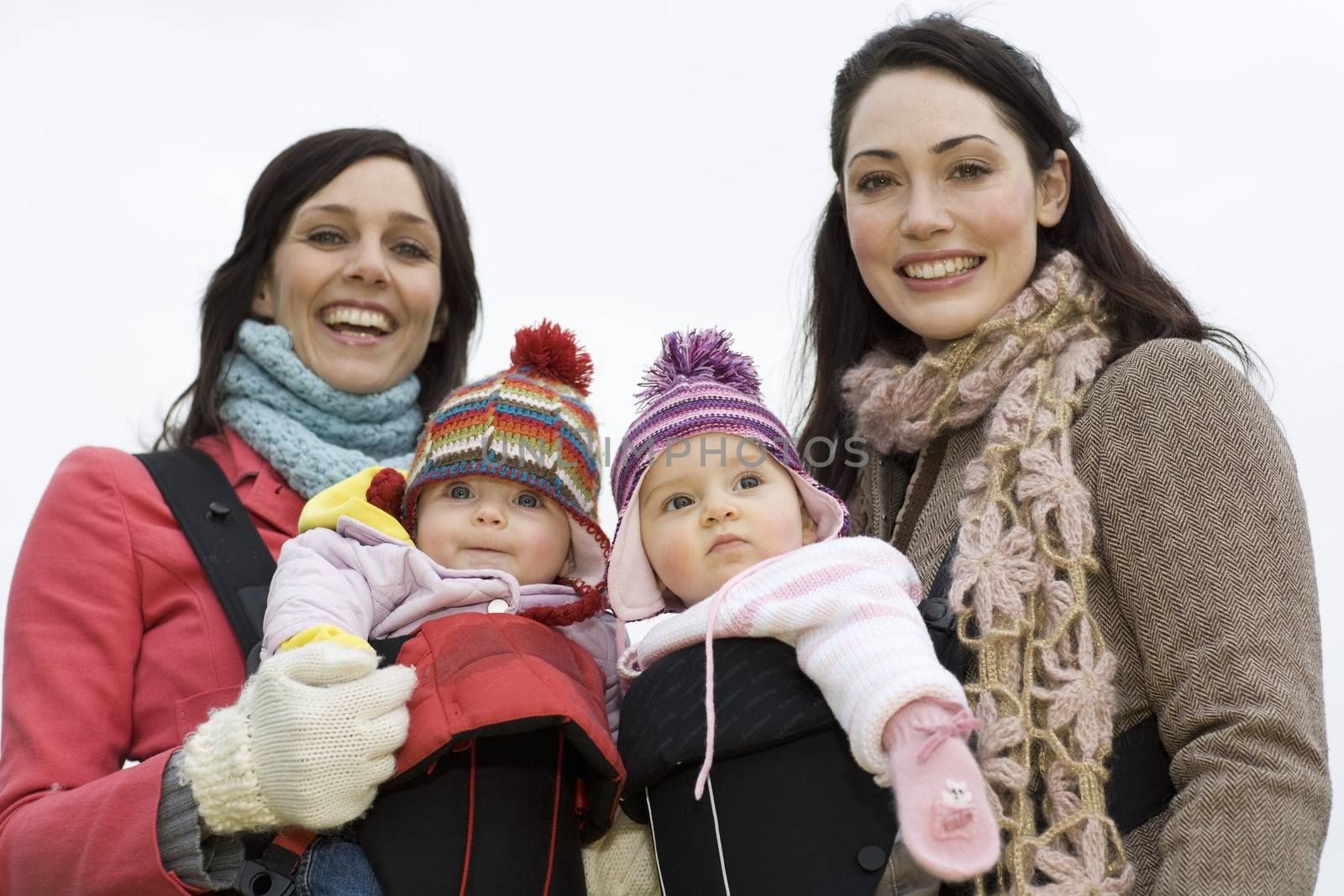 Two mothers with babies in baby carriers by moodboard