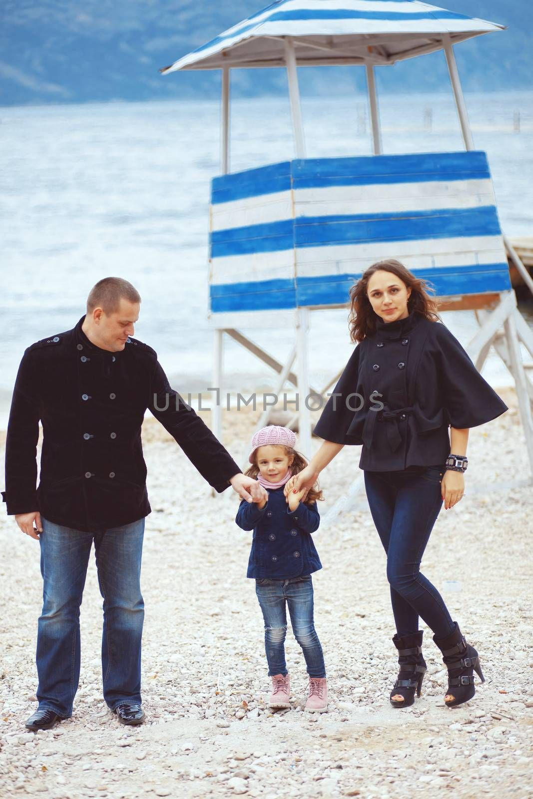 Portrait of happy young family walking with their child near sea in the city, still life photo
