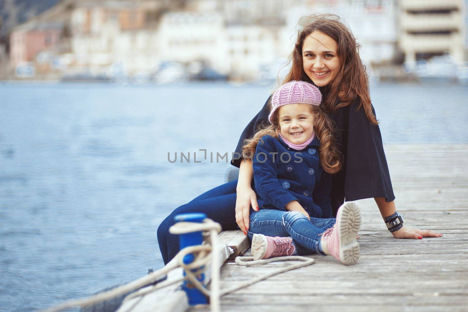 Portrait of mother with herdaughter playing on berth near sea in the city, still life photo
